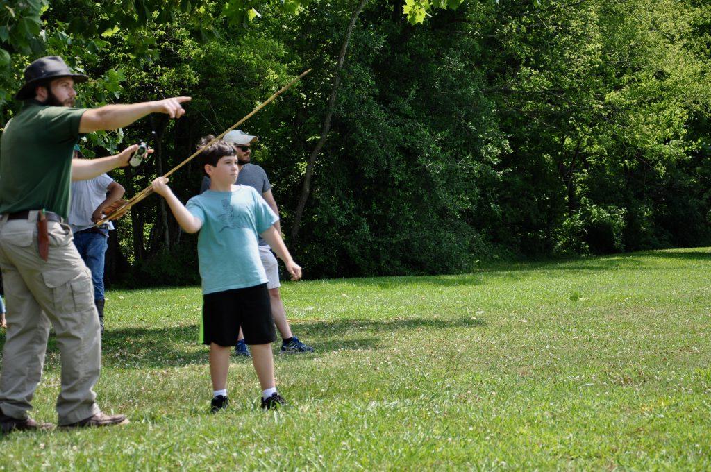 Boy practicing with atlatl.