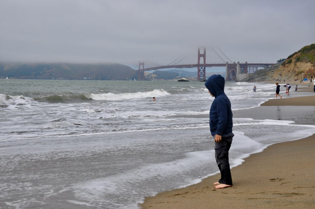 Boy standing on Baker Beach near Golden Gate Bridge